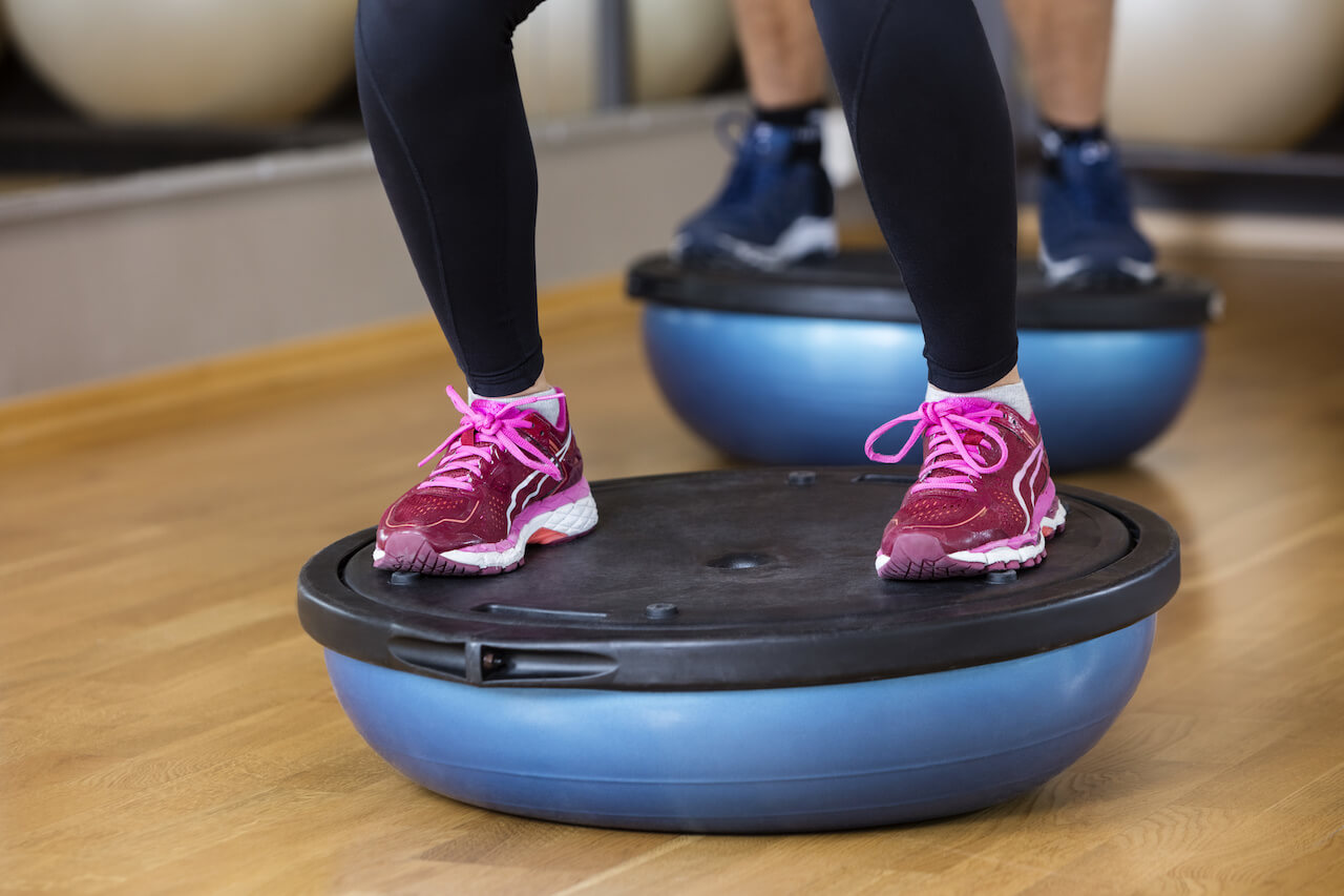 Low Section Of Woman Standing On Bosu Ball