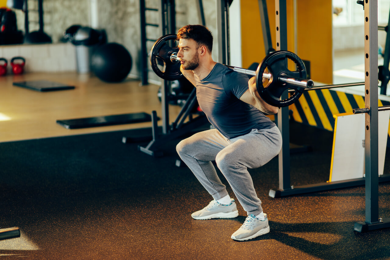 Handsome man doing squats with weights in the gym